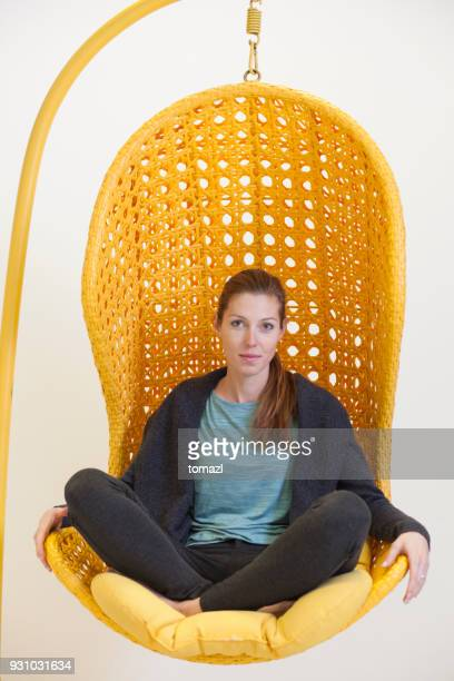 Woman in an creative office hanging chair