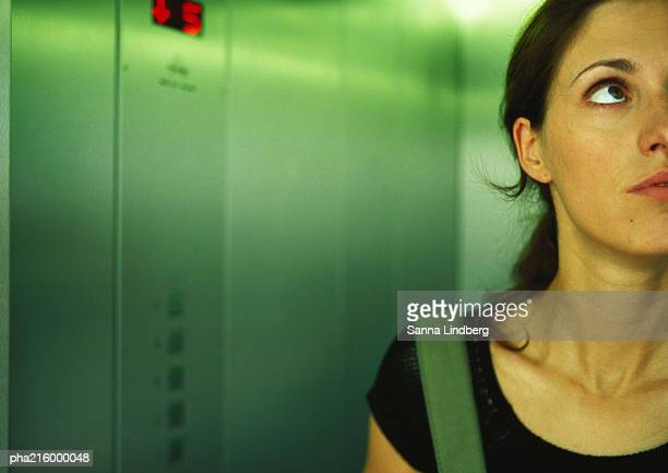 Woman in an elevator, head and shoulders, partial view, close-up.