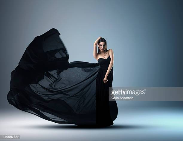 a woman in an evening dress with flowing fabric - evening gown stock pictures, royalty-free photos & images