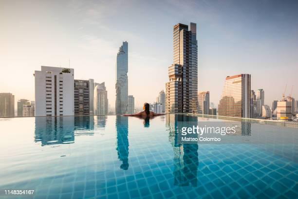 woman in an infinity pool admiring bangkok skyline - シーロム ストックフォトと画像