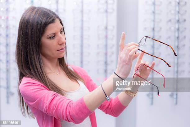 Woman in an optician shop choosing glasses