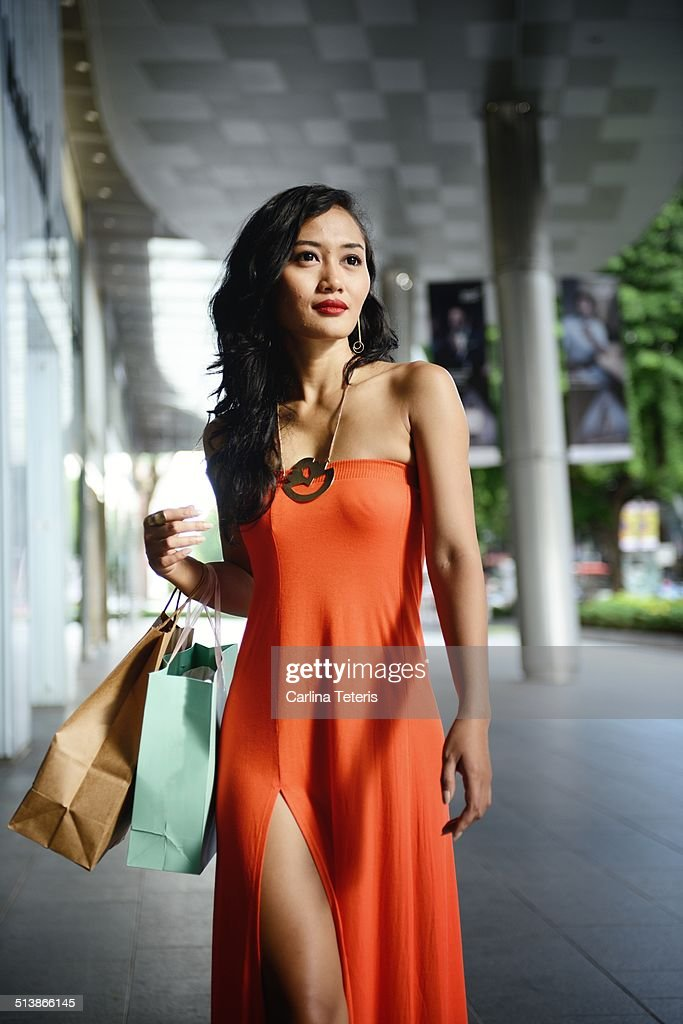 Woman in an orange dress in front of a mall : Stock Photo