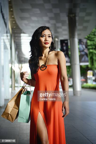 Woman in an orange dress in front of a mall