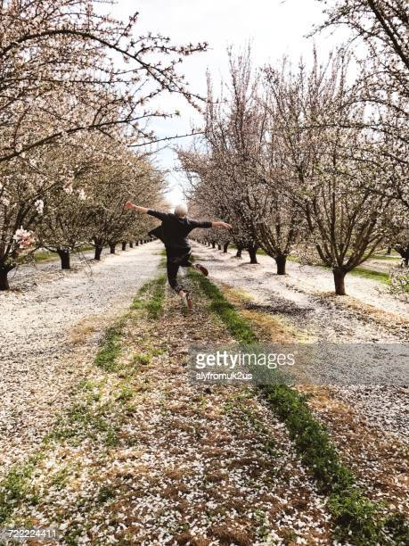 Woman in an orchard jumping in air, California, America, USA