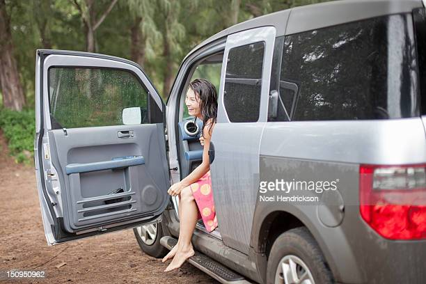 A woman in an SUV at the ocean
