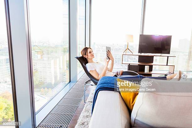 Woman in apartment using digital tablet