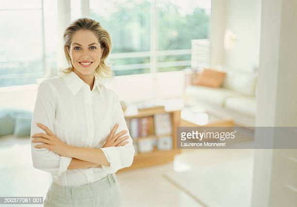 woman in apartment with arms crossed smiling, portrait - blouse ストックフォトと画像