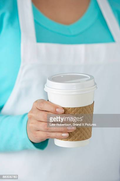 Woman in apron holding to go cup of coffee