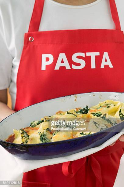 Woman in apron serving baked pasta dish