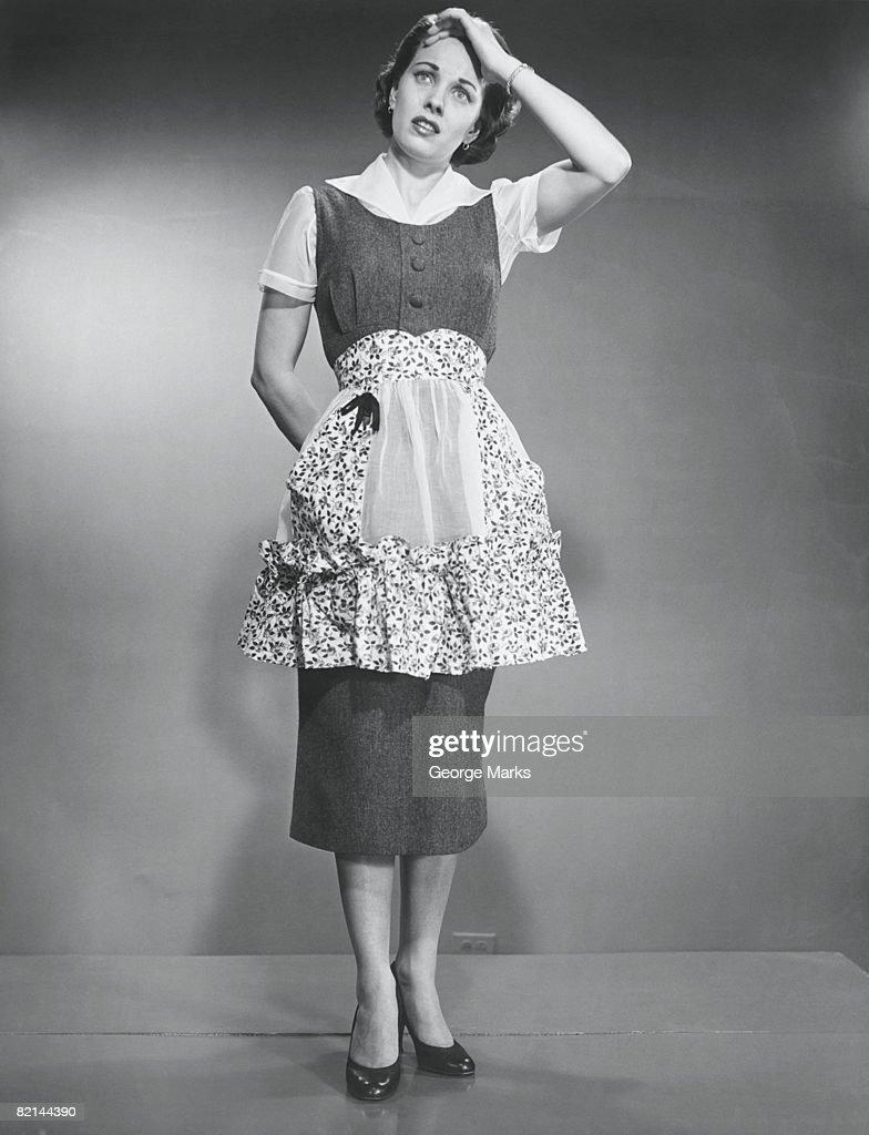Woman in apron touching head, (B&W) : Stock Photo