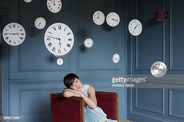 woman in armchair with hanging clocks above - dreaming stock pictures, royalty-free photos & images