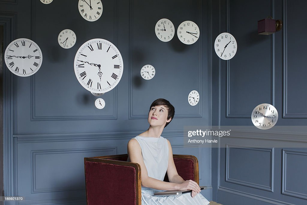 Woman in armchair with hanging clocks above : Stock Photo