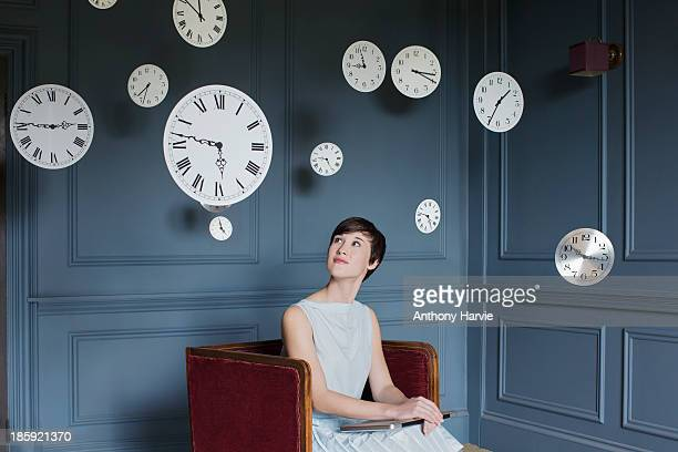 woman in armchair with hanging clocks above - día fotografías e imágenes de stock