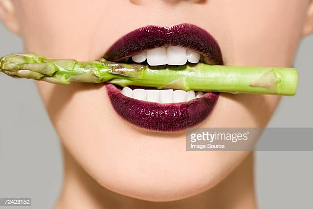 Woman in asparagus in her mouth