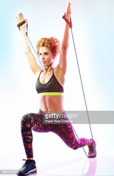 woman in athletic gym attire, holding a resistance band and creating tension between her leg and arms for a strong stretch. - エクササイズ用具 ストックフォトと画像