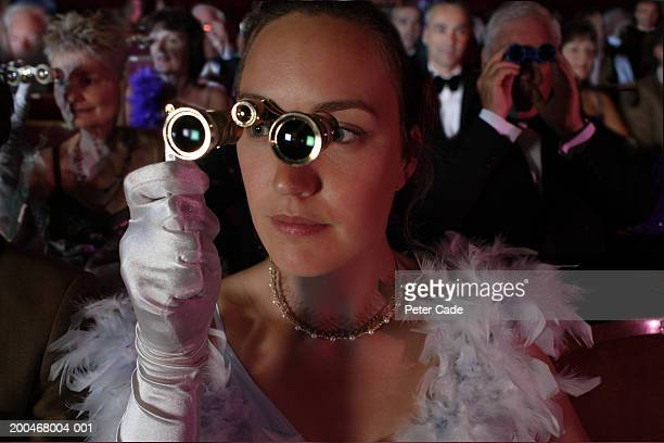 woman in audience using opera glasses - high society stock pictures, royalty-free photos & images