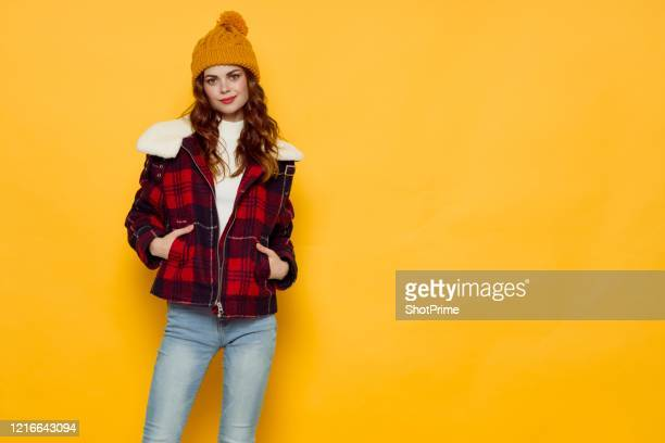 a woman in autumn clothes and put his hands in the pockets of his jacket. - red trousers stock pictures, royalty-free photos & images