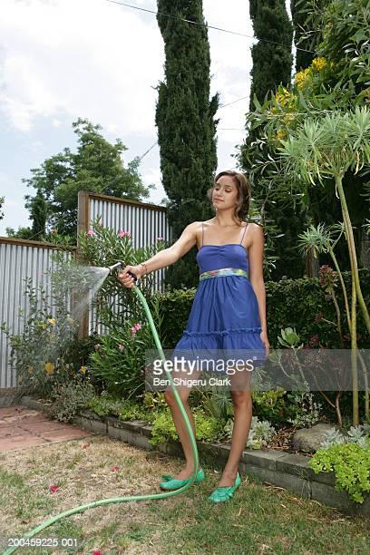 Woman in backyard watering plants