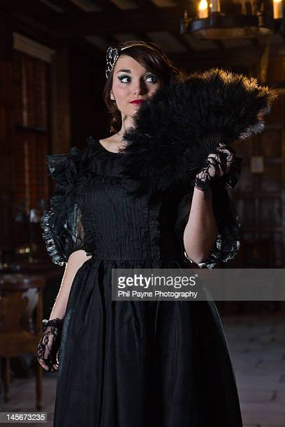 Woman in ball gown with feather fan
