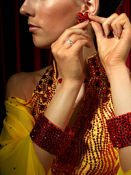 Woman in ballroom dancing costume, adjusting earring, close-up
