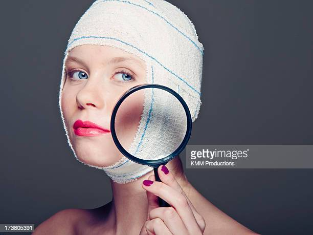 Woman in bandages with magnifying glass