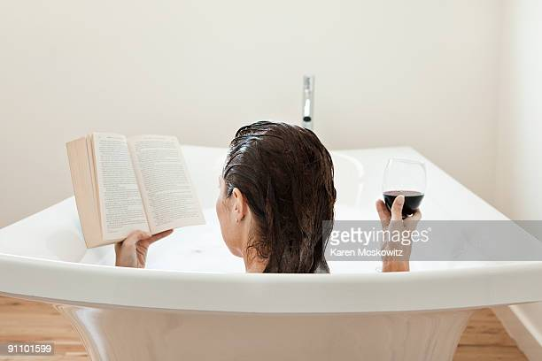 woman in bath reading with glass of wine