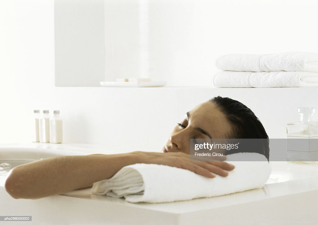 Woman in bath resting head on edge of tub : Stock Photo