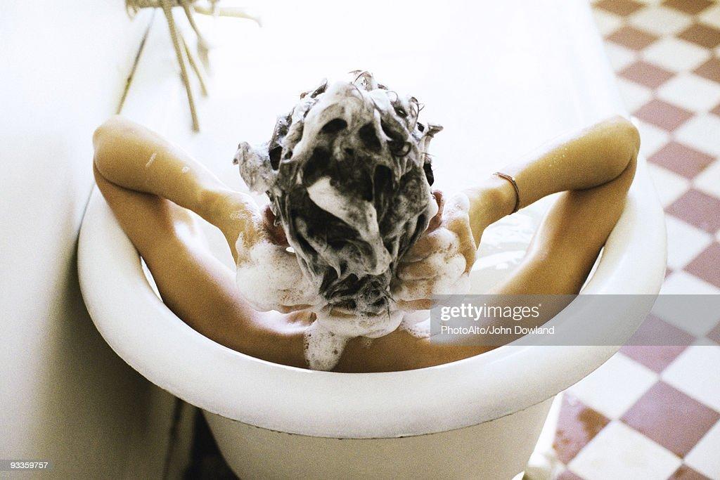 Woman in bath shampooing hair : Stock Photo