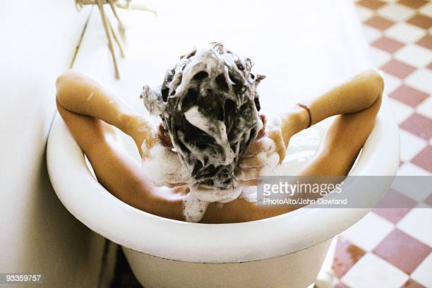 woman in bath shampooing hair - shampoo stockfoto's en -beelden