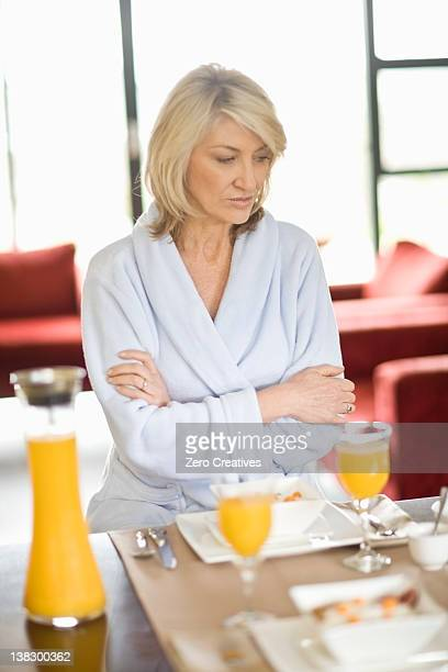 Woman in bathrobe at breakfast table