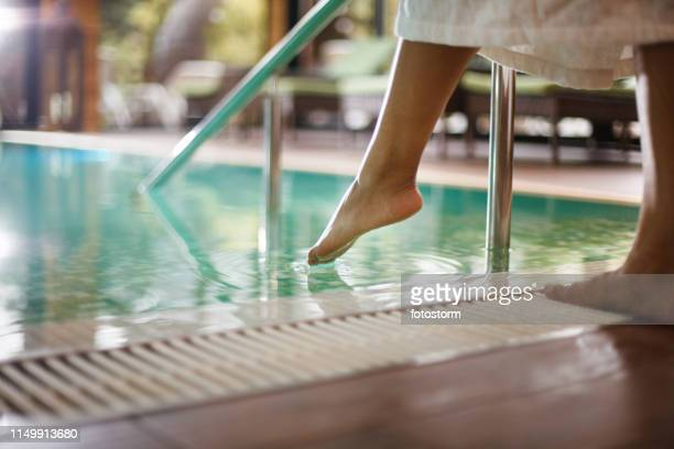 woman in bathrobe dipping toes into swimming pool - toe stock pictures, royalty-free photos & images