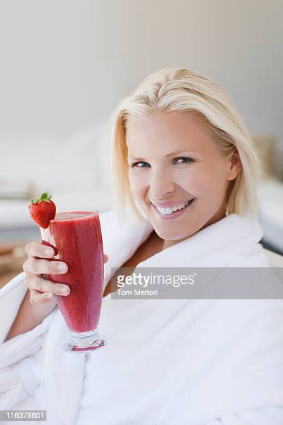 Woman in bathrobe drinking fruit smoothie