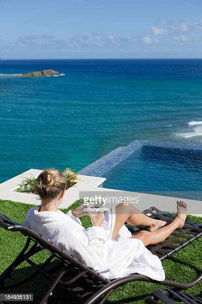 woman in bathrobe drinking morning coffee by an infinity pool