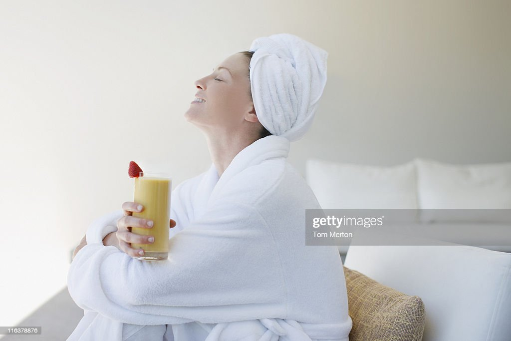 Woman in bathrobe drinking smoothie : Stock Photo