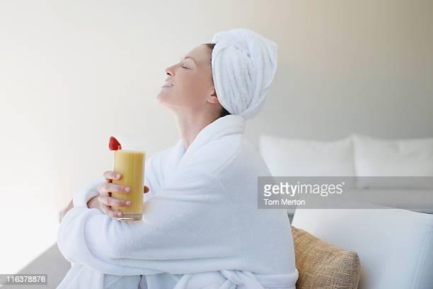 Frau in Bademantel trinken smoothie