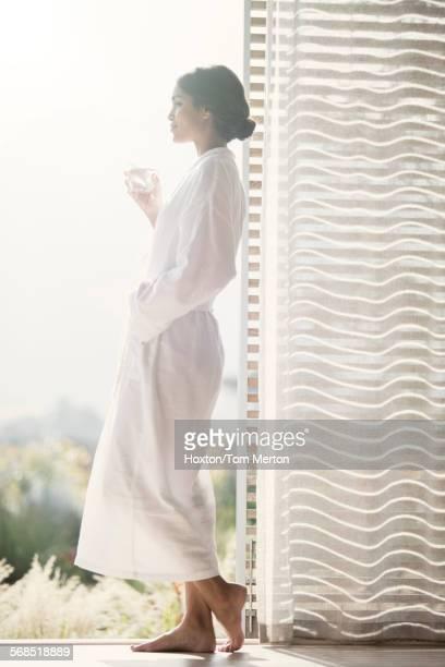 Woman in bathrobe drinking water at open door