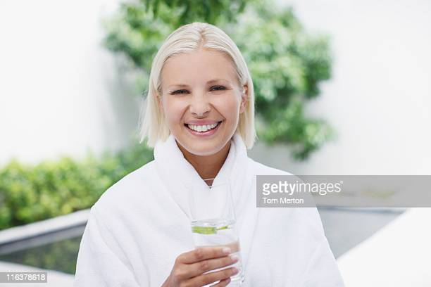 Woman in bathrobe drinking water at poolside