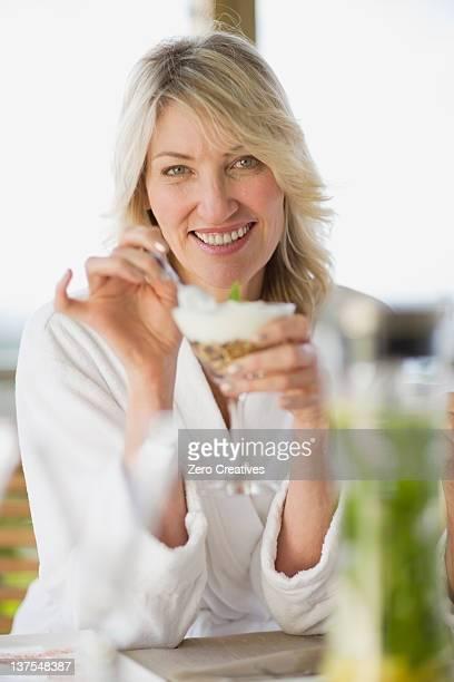 Woman in bathrobe eating breakfast