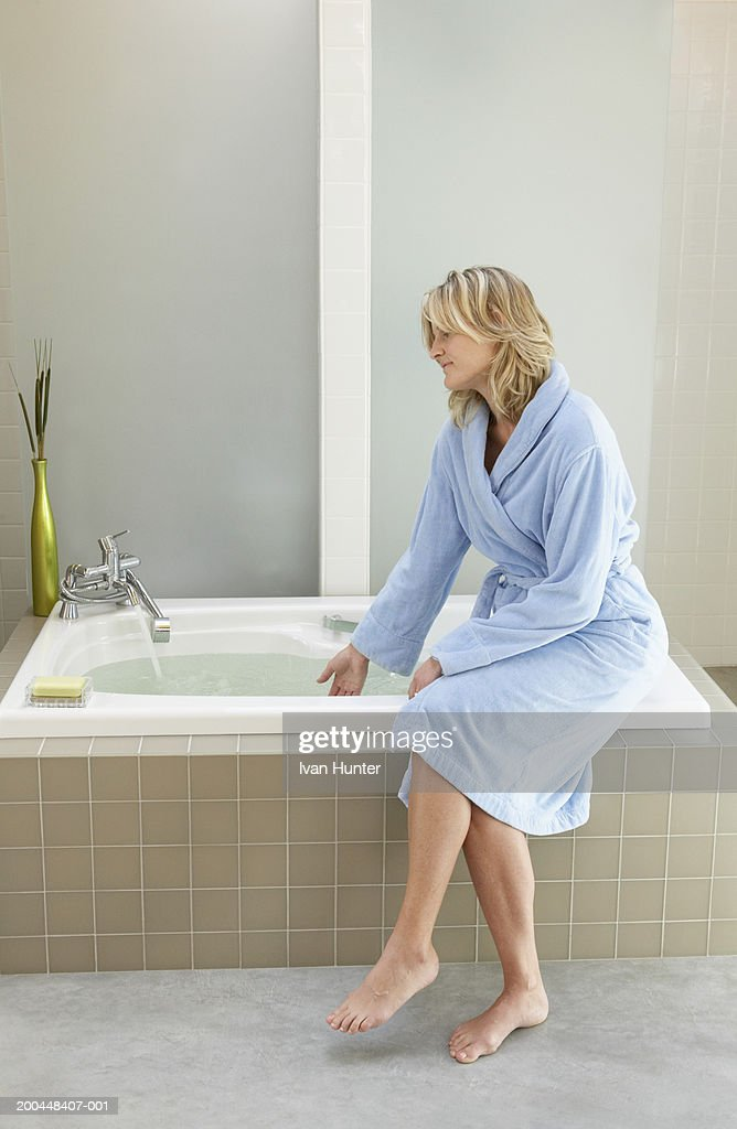 Woman In Bathrobe Filling Bathtub With Water Stock Photo | Getty Images