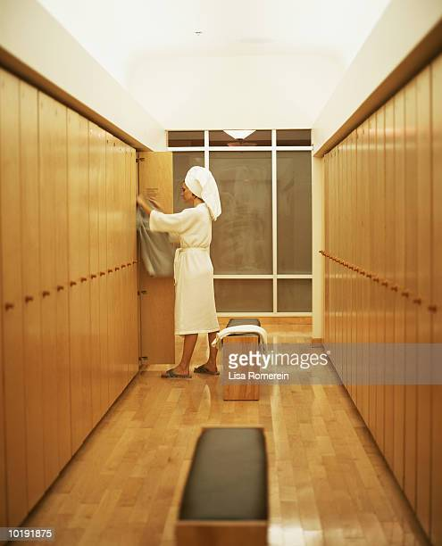 Woman in bathrobe getting dressed in locker room