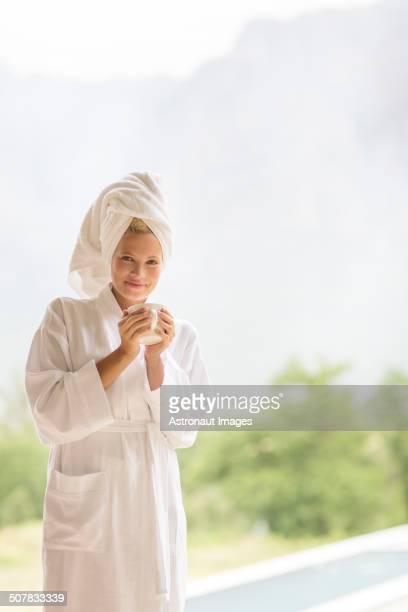 Woman in bathrobe having coffee outdoors