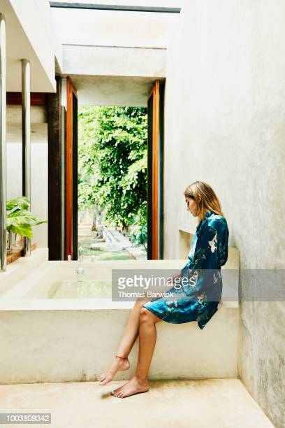 Woman in bathrobe sitting at edge of bathtub