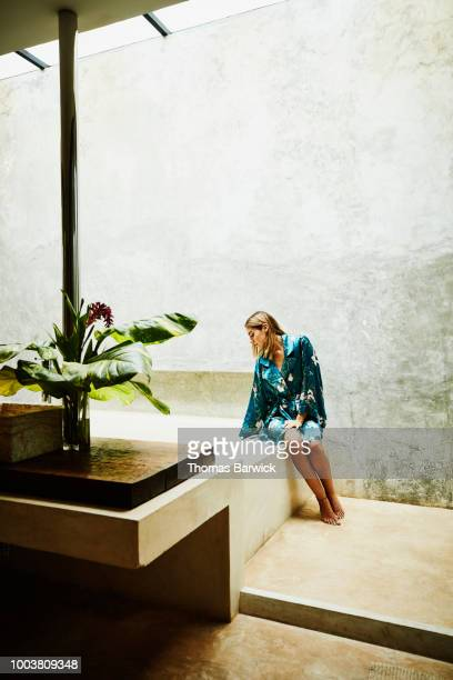 Woman in bathrobe sitting at edge of bathtub testing water