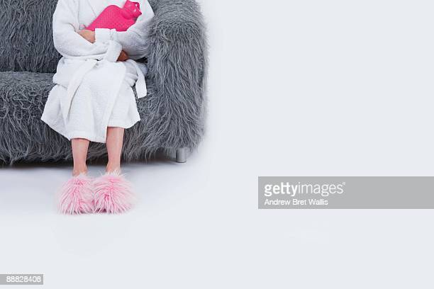 woman in bathrobe sitting on sofa holding hot water bottle - hairy woman stock pictures, royalty-free photos & images