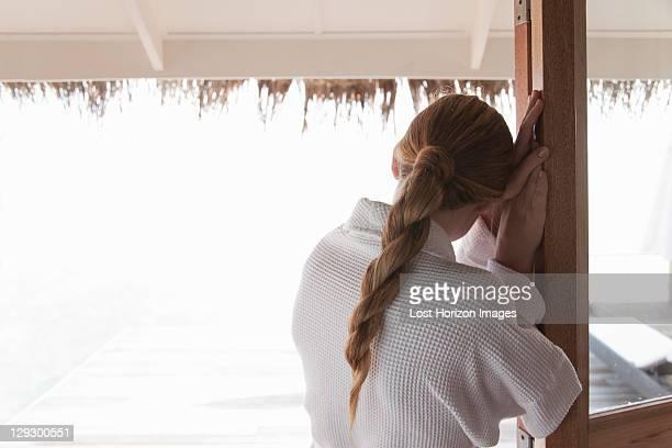 Frau im Bademantel, steht an Tür