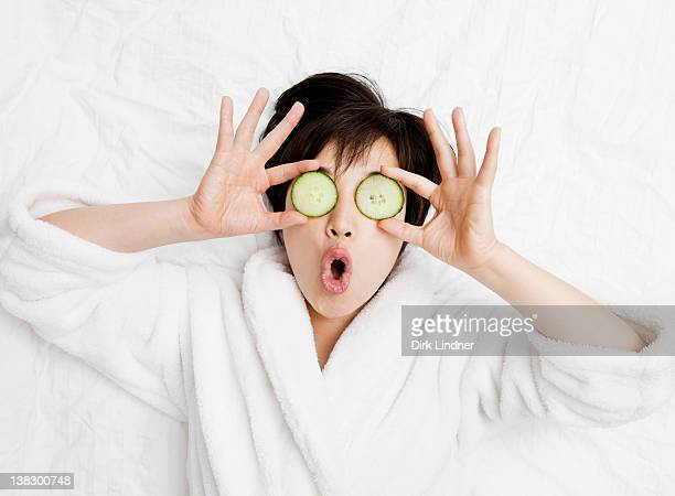 woman in bathrobe with cucumbers on eyes - pepino fotografías e imágenes de stock