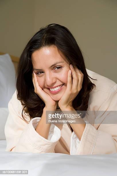 Woman in bathrone lying on bed, portrait