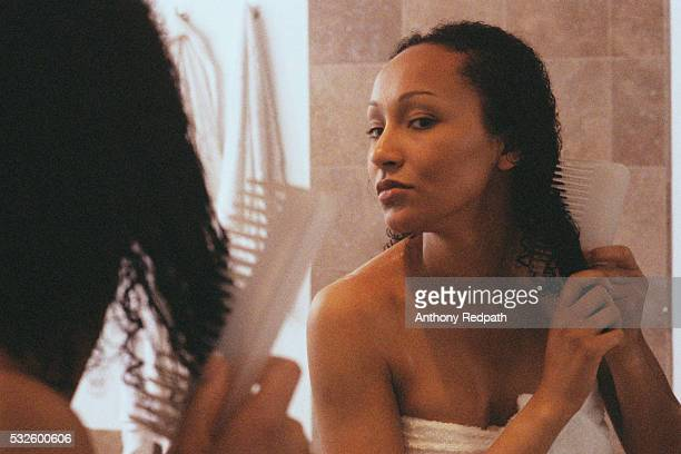 woman in bathroom combing hair - penteando imagens e fotografias de stock