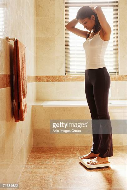Woman in bathroom, standing on weight scale, looking down