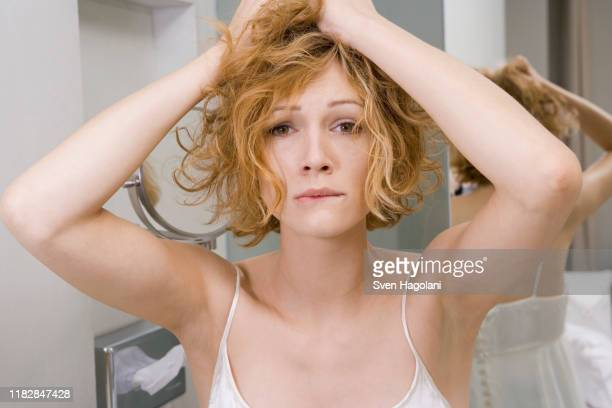 woman in bathroom tearing her hair out - curly hair stock pictures, royalty-free photos & images